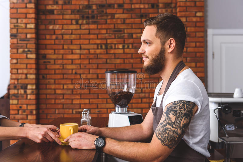 Barista allegro che dà tazza di caffè al cliente fotografia stock