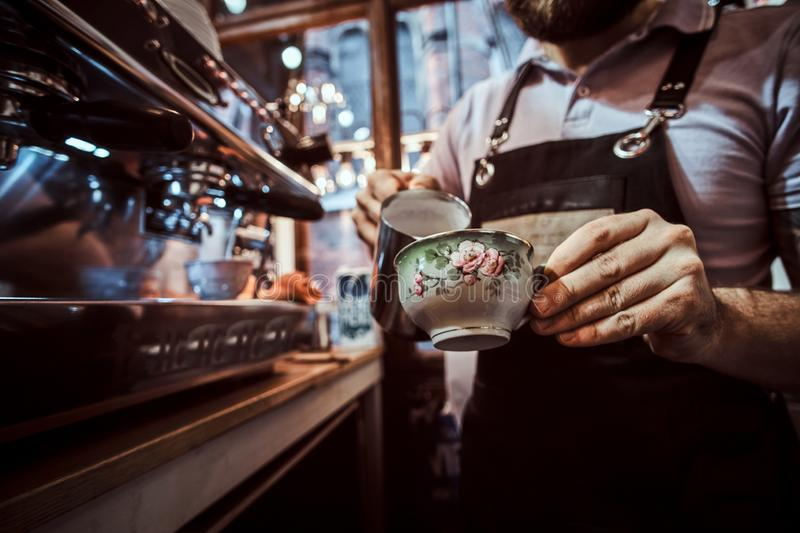 Barista wearing apron making a cappuccino, pouring milk in a cup in a restaurant or coffee shop. Barista in apron making a cappuccino, pouring milk in a cup in a royalty free stock photo