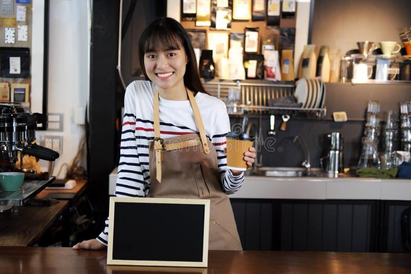 Barista asiático sonriente que sostiene la taza de café en el contador en café fotos de archivo