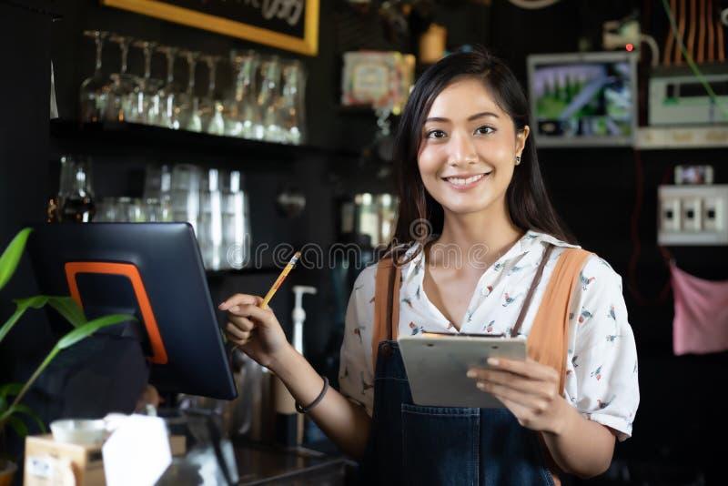 Barista asiatico delle donne che sorride e che utilizza la macchina del caff? nell'alimento e nella bevanda contro- del piccolo i immagini stock libere da diritti