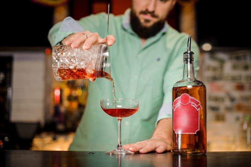 Barista barbuto che versa una bevanda alcolica in un vetro immagine stock libera da diritti