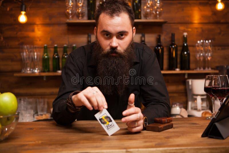 Barista barbuto dei pantaloni a vita bassa che gioca con le sue carte di trucco immagini stock