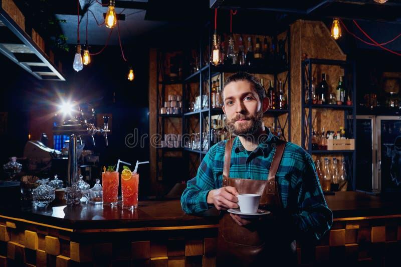 Barista, bartender hipster με ένα φλιτζάνι του καφέ στον καφέ φραγμών στοκ φωτογραφία