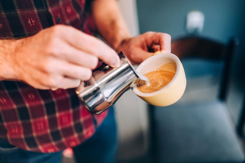 Professional barista and bartender pouring latte foam over coffee, espresso and creating a perfect cappuccino royalty free stock photography
