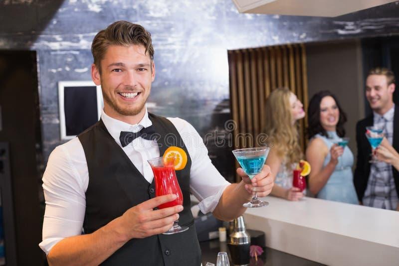 Barista bello che sorride ai cocktail della tenuta della macchina fotografica immagini stock