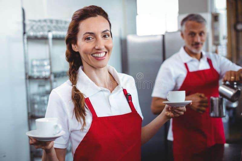 Barista bonito que sostiene las tazas de café con el colega detrás fotos de archivo