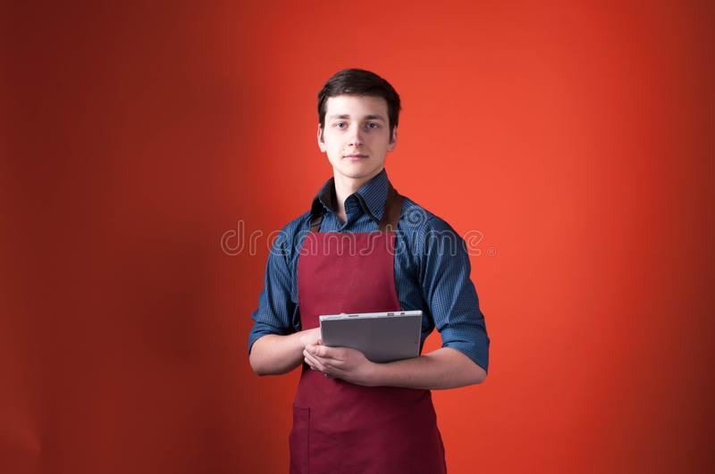 Barista in burgundy apron looking at camera and holding digital tablet on orange background. Handsome barista in burgundy apron looking at camera and holding royalty free stock photography