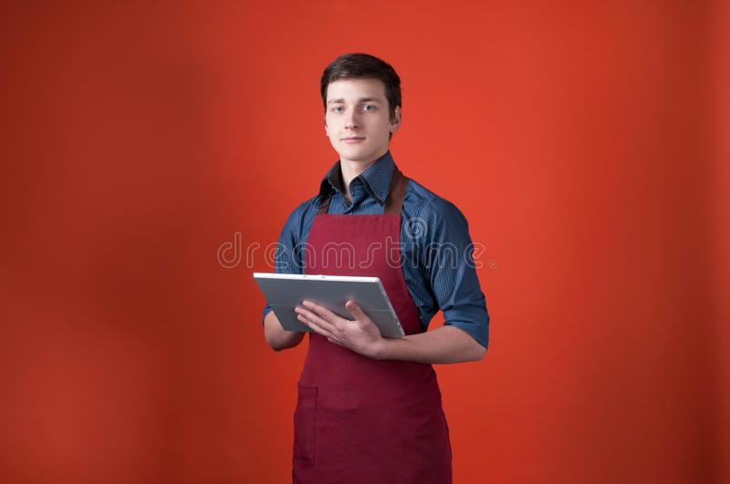 Barista in burgundy apron looking at camera and using digital tablet on orange background. Handsome barista in burgundy apron looking at camera and using digital royalty free stock image