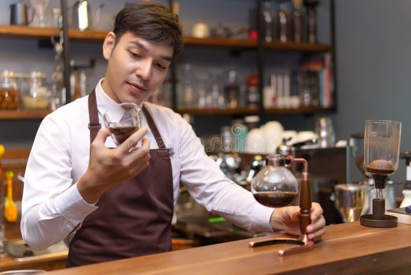Barista caucasico bello che tiene un caffè di versamento della tazza con la SYP fotografie stock