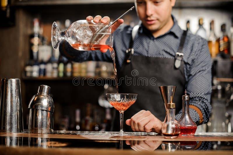 Barista che aggiunge bevanda alcolica rossa nel vetro di cocktail immagine stock