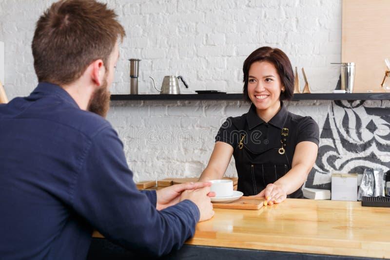 Barista che chiacchiera con l'ospite ed il caffè servente fotografie stock libere da diritti