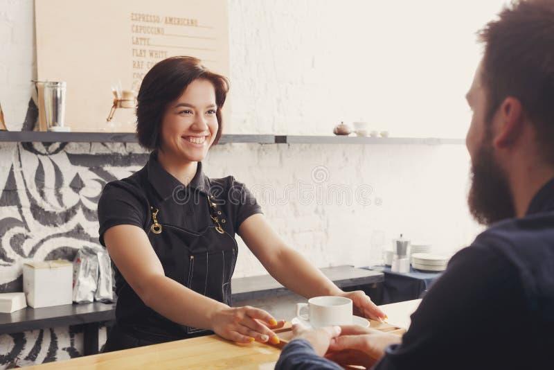 Barista che chiacchiera con l'ospite ed il caffè servente fotografia stock libera da diritti