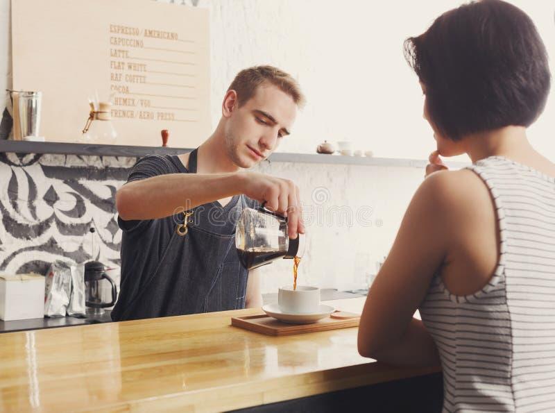 Barista che chiacchiera con l'ospite ed il caffè servente fotografia stock