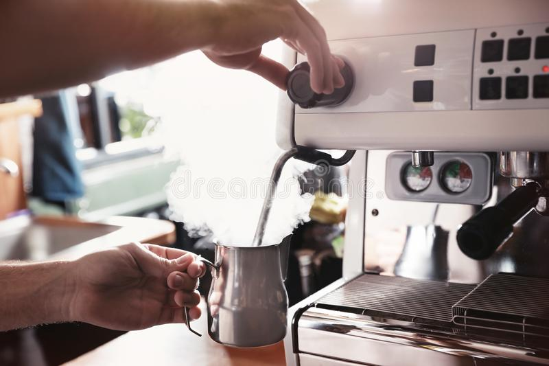 Barista che cuoce a vapore latte in brocca del metallo con la bacchetta della macchina del caffè al contatore della barra fotografia stock libera da diritti