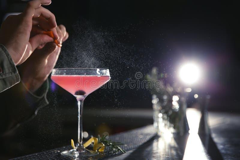 Barista che fa il cocktail cosmopolita di martini al contatore, primo piano immagini stock libere da diritti