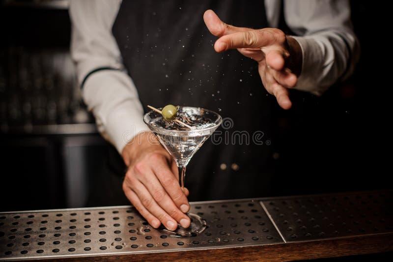 Barista che fa un cocktail fresco e forte di martini di estate con oliva e sale fotografia stock libera da diritti