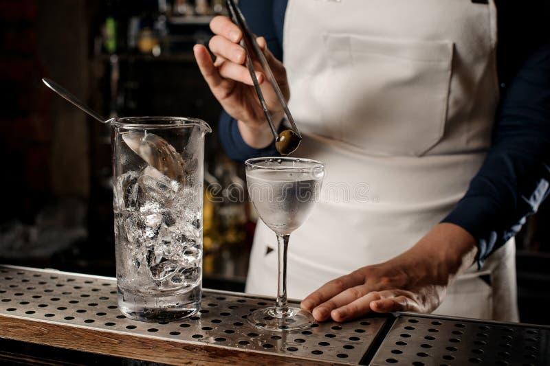 Barista che mette un'oliva in un vetro di cocktail fotografia stock