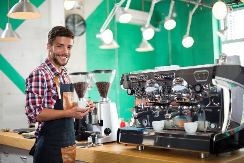 Barista che offre una tazza di caffè alla macchina fotografica in un caffè immagine stock