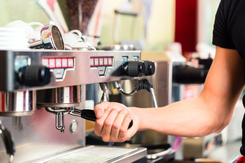 Barista che prepara caffè espresso alla macchinetta del caffè fotografia stock libera da diritti