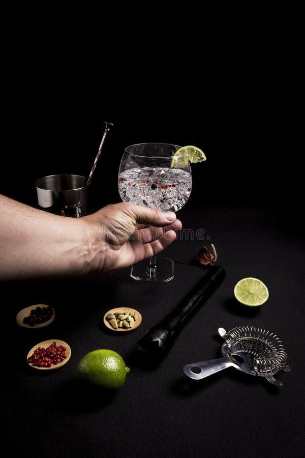 Barista che prepara un gin e un cocktail del tonico su un fondo nero accanto ai suoi ingredienti immagini stock