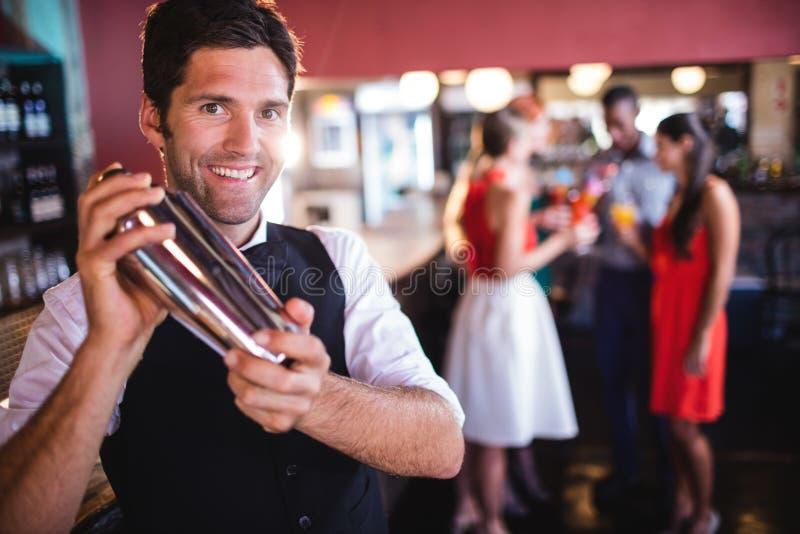Barista che scuote il miscelatore del cocktail in night-club immagini stock libere da diritti