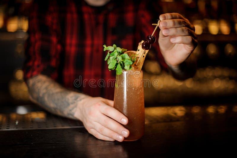 Barista che serve il cocktail della zanna di una cobra con una decorazione fotografia stock