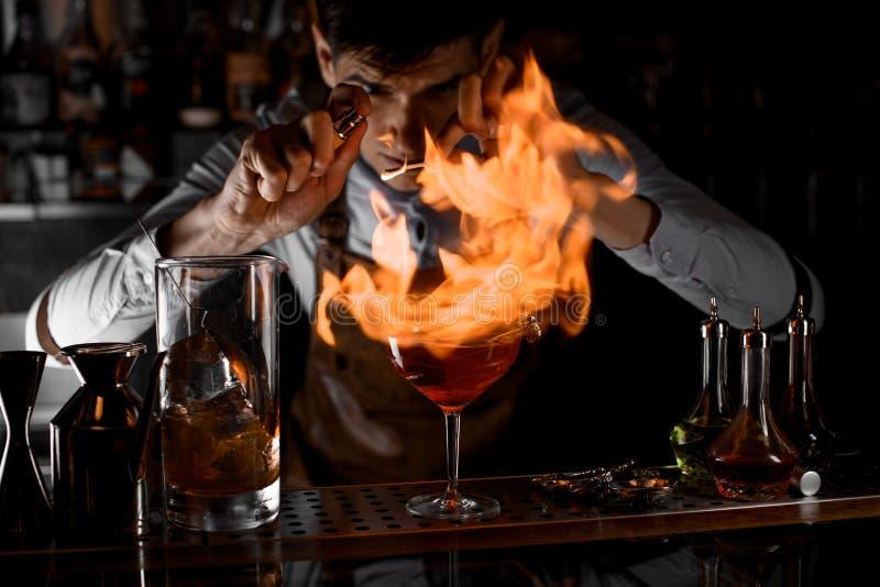 Barista che spruzza sul fuoco intorno al vetro di cocktail immagine stock