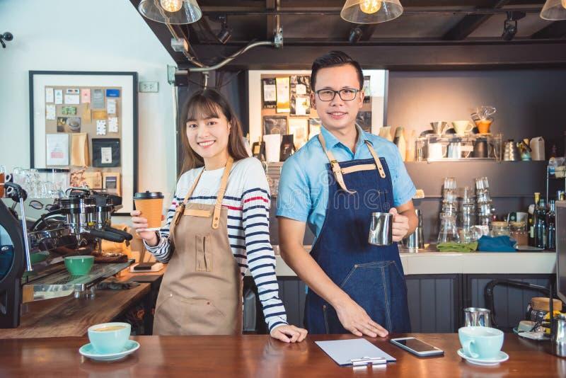 Barista che sta con il sorriso nella loro caffetteria fotografia stock libera da diritti