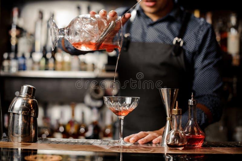Barista che versa bevanda alcolica rossa nel vetro di cocktail fotografie stock