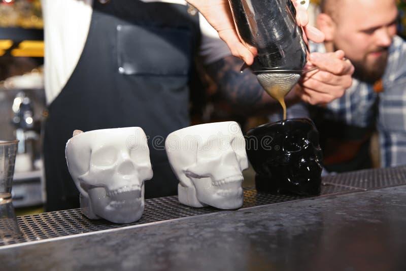 Barista che versa cocktail saporito al contatore in night-club fotografie stock libere da diritti