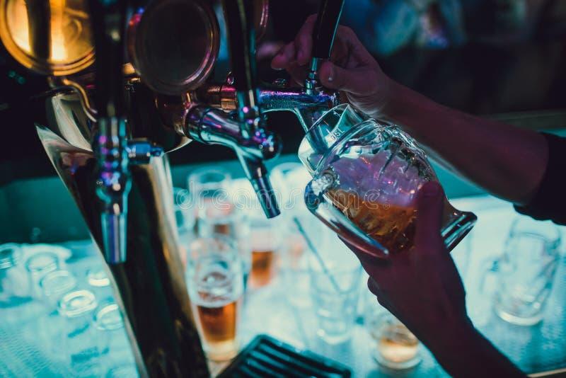 Barista che versa dalla birra fresca del rubinetto nel vetro in pub fotografie stock