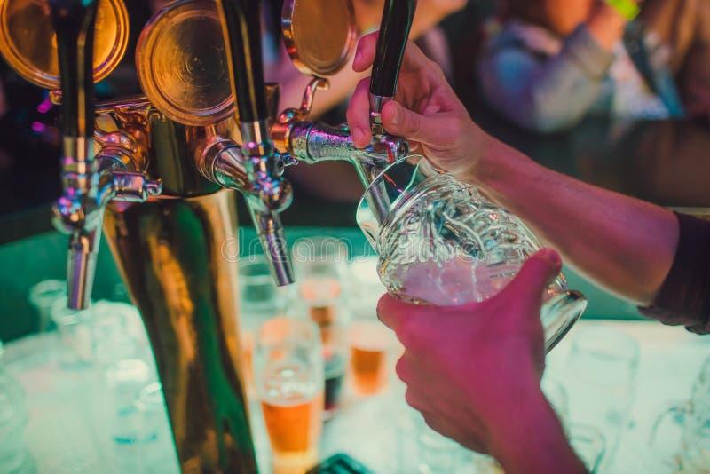 Barista che versa dalla birra fresca del rubinetto nel vetro in pub fotografia stock libera da diritti
