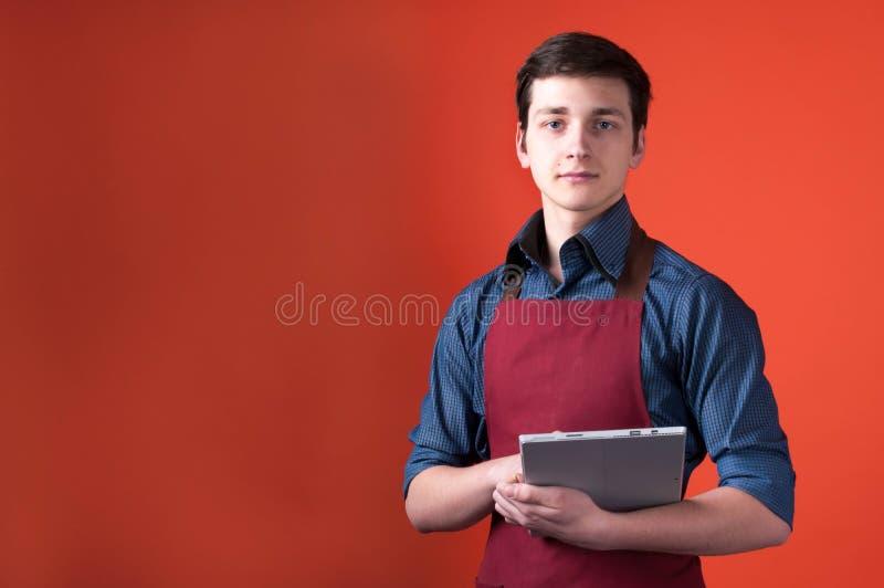 Barista com cabelo escuro no avental azul da camisa e da Borgonha que guarda a tabuleta digital e que olha a câmera foto de stock royalty free