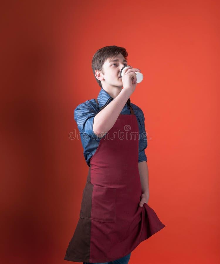 barista con el pelo oscuro en café de consumición del delantal rojo con la taza de papel y mirada lejos en el fondo coralino del  imágenes de archivo libres de regalías