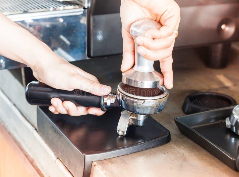 Barista con el pisón para hacer el café express con estilo del vintage imagenes de archivo