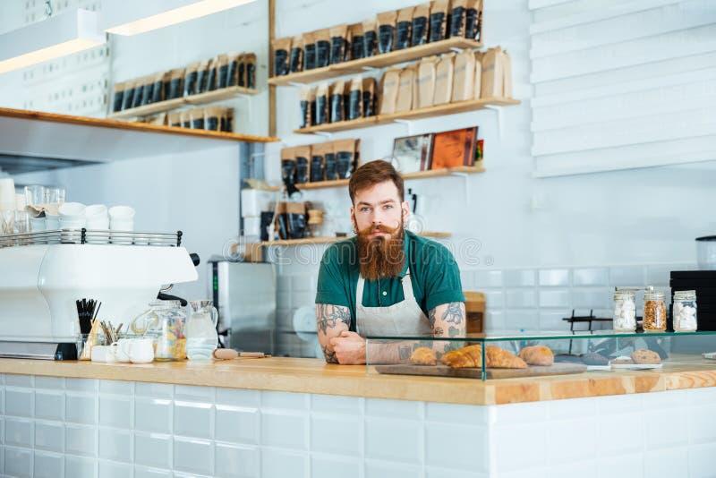Barista con la barba y el bigote que se colocan en cafetería imágenes de archivo libres de regalías