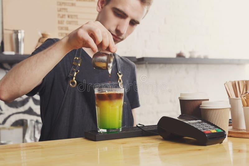 Barista concentrato che fa il cocktail del caffè immagini stock