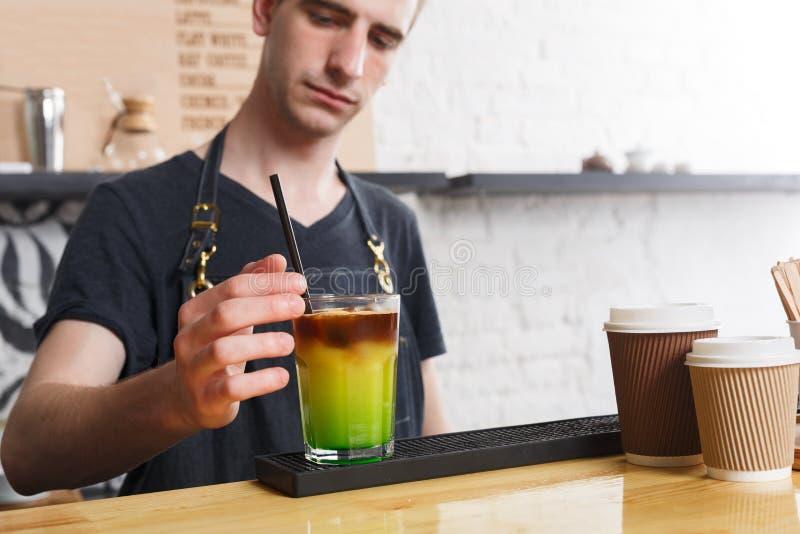 Barista concentrato che fa il cocktail del caffè al contatore del caffè immagine stock libera da diritti