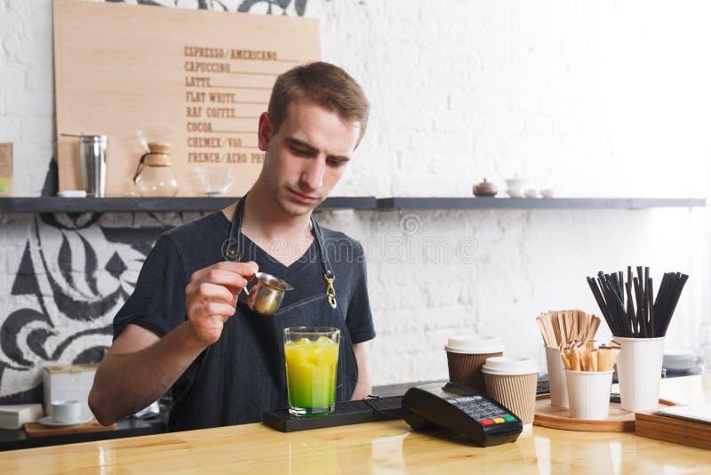 Barista concentrato che fa il cocktail del caffè al contatore del caffè immagini stock