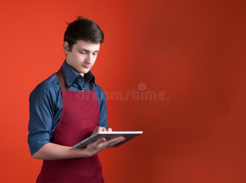 barista considerável no avental de Borgonha usando a tabuleta digital no fundo coral da cor imagens de stock royalty free