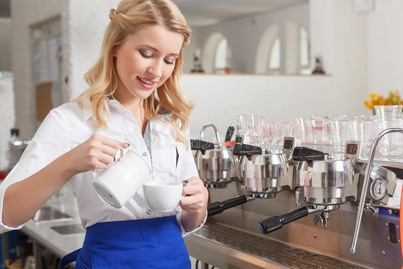 Barista consideravelmente fêmea que derrama algum leite no copo imagem de stock