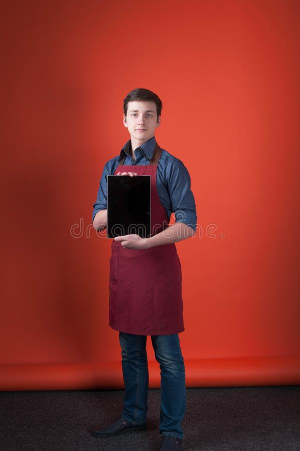 Barista with dark hair in blue shirt, jeans and burgundy apron holding digital tablet. Young barista with dark hair in blue shirt, jeans and burgundy apron stock image