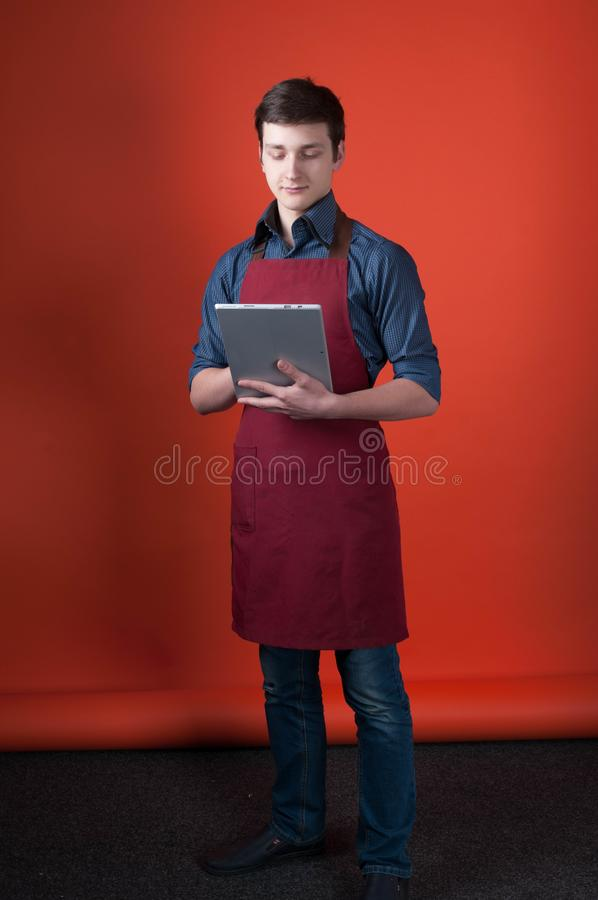 Barista with dark hair in burgundy apron holding and looking at digital tablet in photo studio stock photography