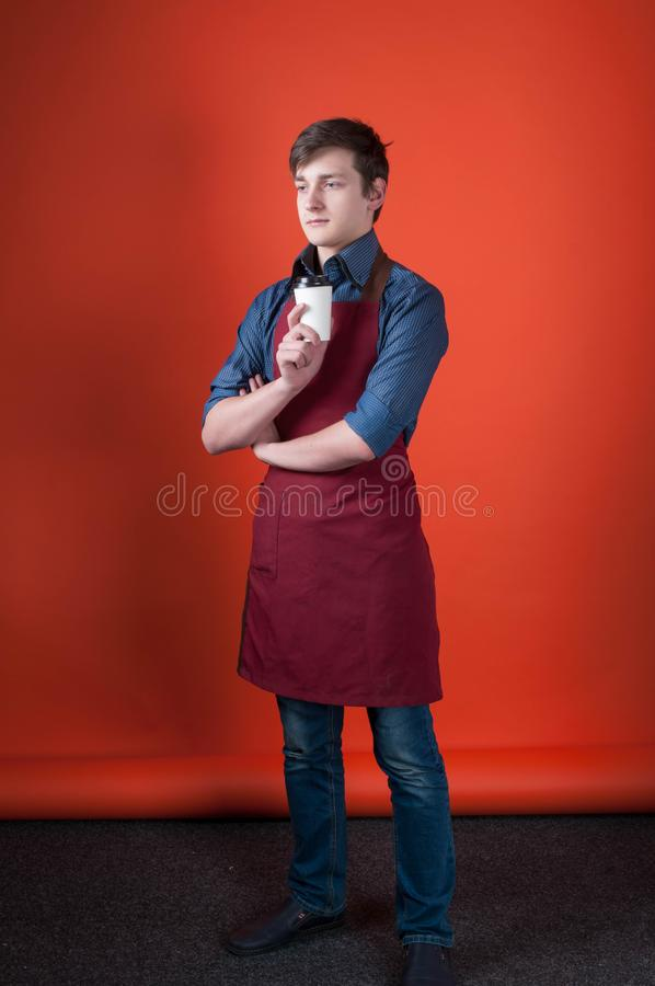 barista with dark hair in burgundy apron holding paper cup with coffee and looking away photo studio royalty free stock photos
