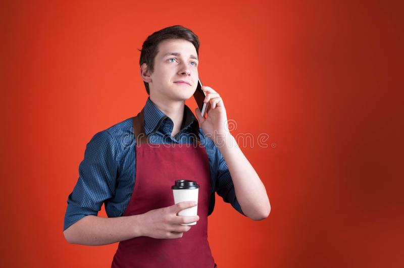 Barista with dark hair in burgundy apron holding paper cup with coffee and talking on smartphone. Handsome barista with dark hair in burgundy apron holding paper stock images