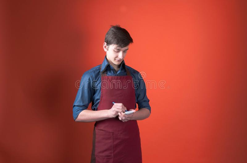 Barista with dark hair in red apron writing in notebook with pen and on colal background with copy space stock images