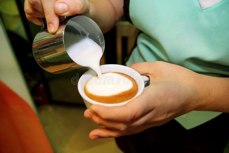 Barista, das Cappuccino in seiner Kaffeestube oder in Café macht lizenzfreie stockfotografie