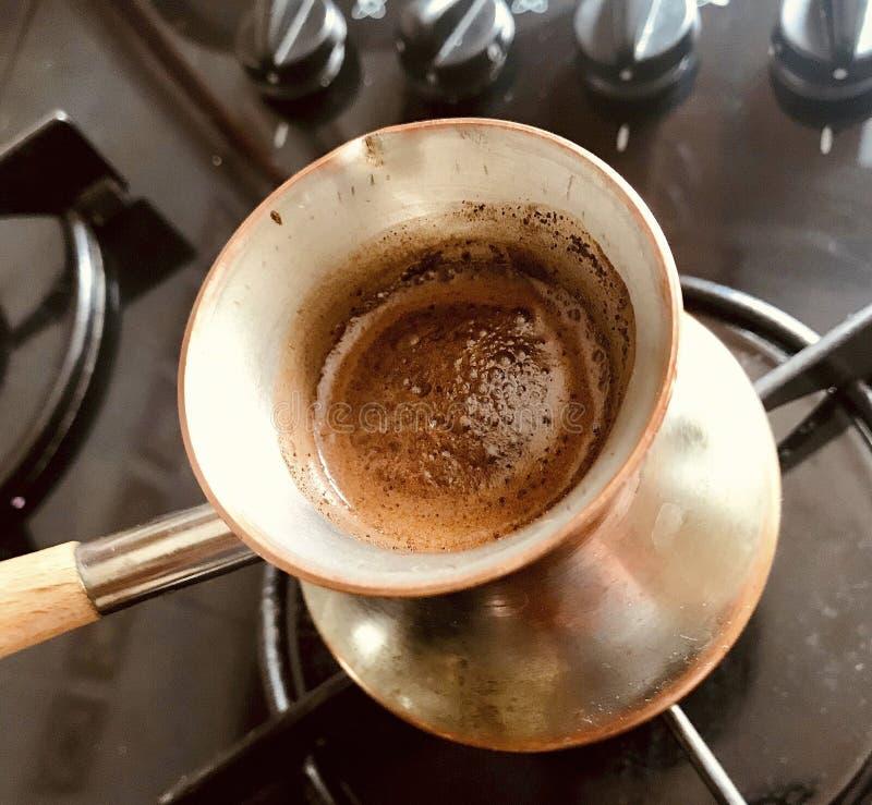 Barista, das heißes geschmackvolles Getränk vom kupfernen Türken vorbereitet stockfotografie