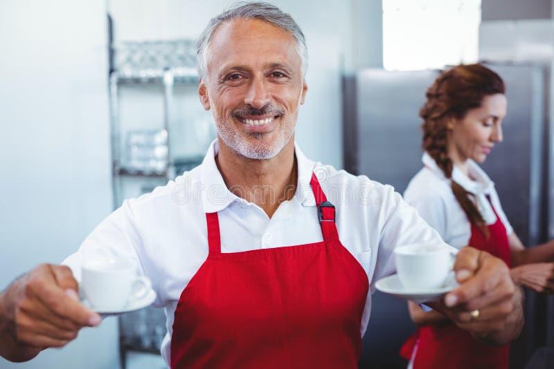 Barista de sorriso que guarda xícaras de café com colega atrás imagens de stock royalty free