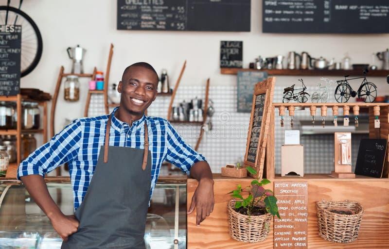 Barista de sorriso que inclina-se no contador em um café imagens de stock